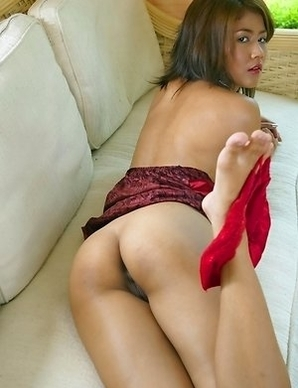 Jasmine Mookjai lies on her sofa in a maroon outfit. She starts to feel very kinky and she begins rubbing on her sexy body.