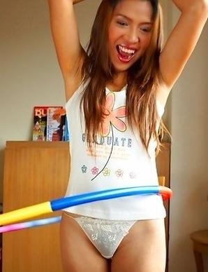 Sexy girl Koko Tongpu has on panties with a shirt. She has a hula hoop around her waist and she shows you how to work it.
